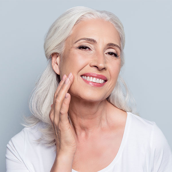 Mature woman putting cream on her face