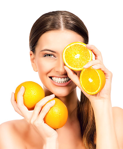 woman holding oranges close to her face