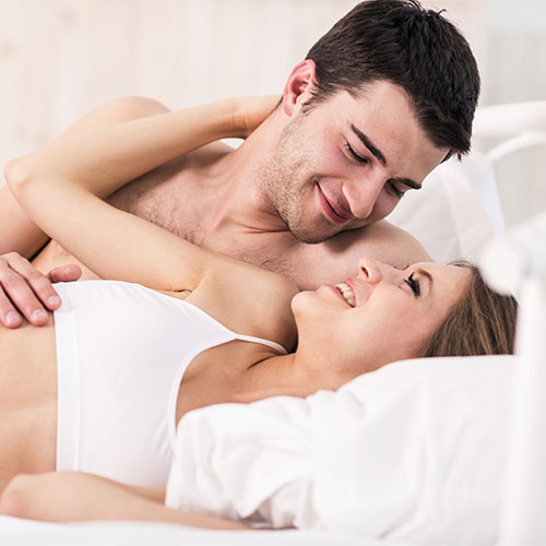man and woman huging and looking adoringly at each other in bed.
